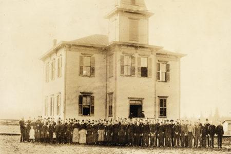 На фотографии студенты и преподаватели Friends Pacific Academy — среди них будущий президент США Герберт Гувер, 1887 г. Четыре года спустя, в 1891 году, открылся Pacific College; здание на фотографии называлось просто «Здание колледжа». Спустя какое-то время его переименуют в «Гувер Холл» (Hoover Hall).