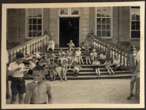 Дети, многие из которых были еврейскими беженцами из Германии, отдыхают на ступеньках квакерской школы-пансиона в Эрде. Ок. 1933-1339 гг.